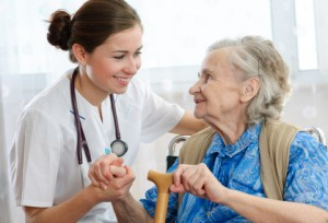 krankenpflegerin und alte Frau im Rollstuhl halten sich an der Hand und lächeln sich an